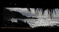 Surf breaking on rugged El Hierro coastline looking through shelter,Canary islands.