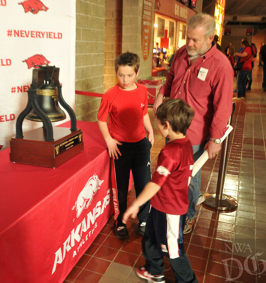 NWA Democrat-Gazette/MICHAEL WOODS &bull; @NWAMICHAELW<br /> John David Moore, 11, Davis Moore, 7, and Ben Moore from Bentonville, take a look at the Liberty Bowl Trophy on display in the concourse at Bud Walton Arena Saturday, January 30, 2016.  The trophy will be on display for photos Sunday at the women&rsquo;s basketball against No. 13 Mississippi State beginning at 1 p.m. through the end of the half on the South Concourse.