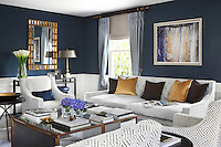 The living/reception room has been richly furnished with dark blue silk wallpaper, inspired by the Tyrrhenian seas, above bespoke panelling painted white