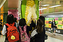 School girls touch a column displaying a giant corn in the Tokyo Metro passageway in Shinjuku on September 1, 2015, Tokyo, Japan. The Central Union of Agricultural Co-operatives (JA-ZENCHU) is promoting Japanese vegetables with the vegetable columns and a massive 80 meter ''Wall Farmer's Market'' information poster until September 6th. (Photo by Rodrigo Reyes Marin/AFLO)