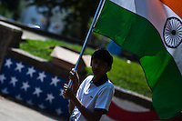 A boy holds one indian flag while he  arrives to a meeting for the annual Indian independence day parade in New Jersey,  August 11, 2013. Photo by Eduardo Munoz Alvarez / VIEWpress.