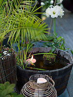 An oak cask makes an attractive water feature on the terrace, with a floating candle illuminating the plants