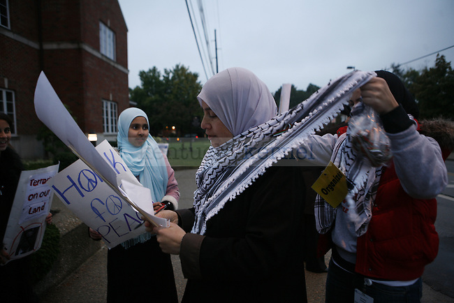 "Rasmieh Suleiman reads a protest sign while her daughter, Kawthar, a senior biology student, helps tie her mother's wrap, during a protest outside the Singletary Center on Wednesday, Oct. 14, 2009. The Suleimans came out to show their support for the Palestinian people and protest former Israeli Prime Minister Ehud Olmert's speech and appearance at UK. ""I think it's important for people to know he's a mass murderer,"" Kawthar said. ""For him to come speak at my university and for me not to speak out would speak volumes of me."""