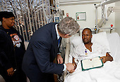 Washington, DC - December 22, 2008 -- United States President George W. Bush shakes the hand of United States Army Sergeant First Class Neal Boyd of Haynesville, Louisiana, after presenting him a Purple Heart during a visit Monday, December 22, 2008, to  Walter Reed Army Medical Center, where the soldier is recovering from injuries received in Operation Iraqi Freedom.  Looking on his SFC Boyd's wife, Joyce.  .Credit: Eric Draper - White House via CNP