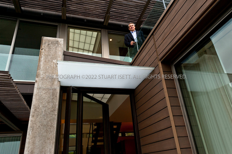 12/24/2010--Seattle, WA, USA..Seattle Architect Stuart Silk, of Stuart Silk Architects, posing at the 'Lake House Residence' on Lake Washington in Seattle's Madison Park neighborhood. ..The client wanted a thoughtfully designed contemporary home that took full advantage of the light and views yet ensured privacy and security. A sixty foot long concrete wall runs through the home defining the gallery which separates the public areas from private. The second floor, housing the master bedroom suite, balances dramatically on the concrete wall below. This home has received 4-Star Built Green certification...©2010 Stuart Isett. All rights reserved.
