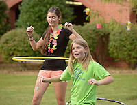NWA Democrat-Gazette/BEN GOFF @NWABENGOFF<br /> Taylor Musi, a Northwest Arkansas Community College student from Rogers, and Amrie Birk, 10, of Centerton hula hoop on Thursday Sept. 24, 2015 during the annual Student Ambassador and Activities Board Welcome Back Luau at the school's Bentonville campus.
