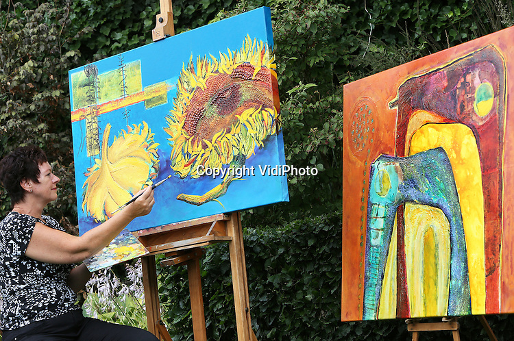 Foto: VidiPhoto<br /> <br /> BEST - Kunstschilder Hera van den Heuvel (57) uit het Brabantse Best zet dinsdag de laatste verfstrepen op de zonnebloemen van Van Gogh. Het schilderij &quot;Ode aan Van Gogh&quot; is een van de drie kunstwerken die ze mag inzenden voor  de prestigieuze expositie Art Square, die van 24 tot en met 29 juli op het Museumplein in Amsterdam wordt gehouden. Hera is de enige Brabantse kunstschilder die haar schilderijen daar mag exposeren. Art Square is dit jaar een eerbetoon aan de bekende kunstenaar Vincent van Gogh, die op 29 juli 1890 overleed, 125 jaar geleden. Hoewel de Brabantse 'Van Gogh' andere technieken gebruikt, lijken stijl en kleur in een aantal van haar kunstwerken op dat van de Hollandse meester. De tentoonstelling in Amsterdam wordt naar verwachting bezocht door duizenden (inter)nationale gasten.