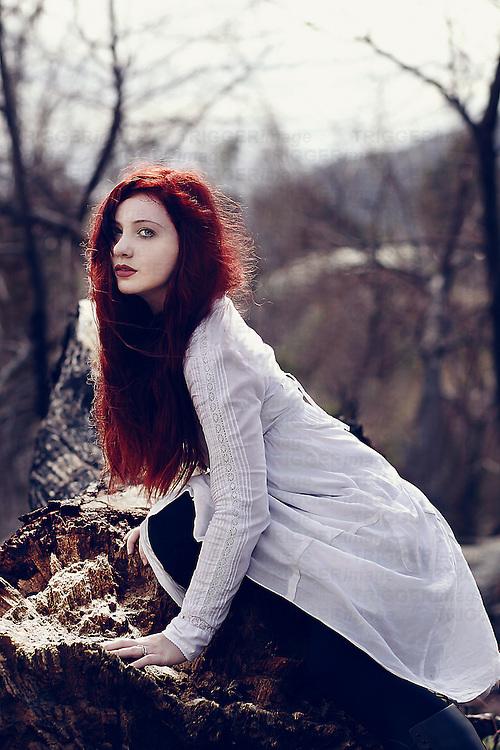 A girl wearing a white dress, sitting on a fallen tree.