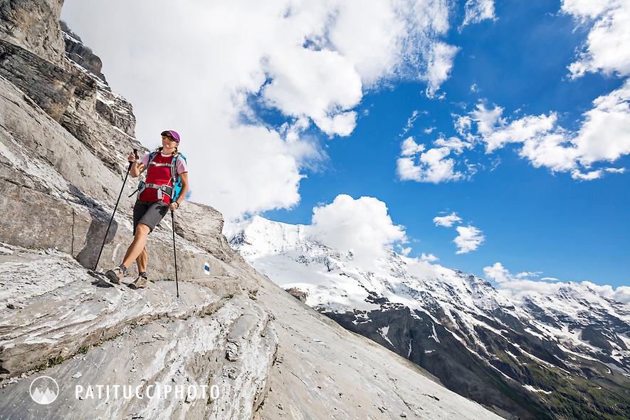 One woman hiking on the Silberhorn Hut Trail, an alpine trail with some very unique sections of wide open, rocky landscapes and extremely exposed sections. Jungfrau Region, from Lauterbrunnen Valley, Switzerland