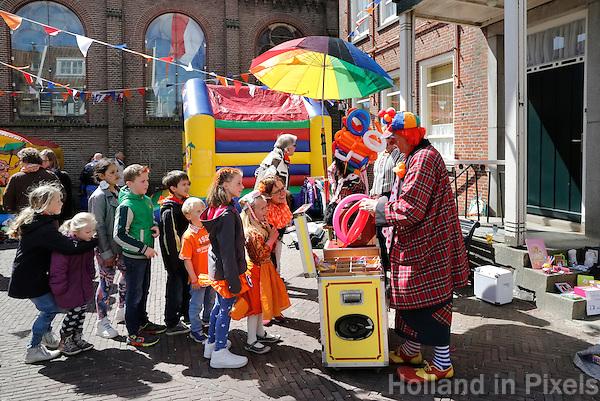 Koningsdag in Marken.  Tijdens Koningsdag dragen veel inwoners van Marken klederdracht met oranje accenten.Clown blaast ballonnen op bij de kerk