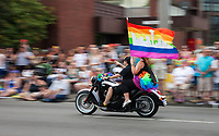 Two Women Riding Motorcycle Holding Rainbow Pride Flag, PrideFest, Seattle, WA, USA.