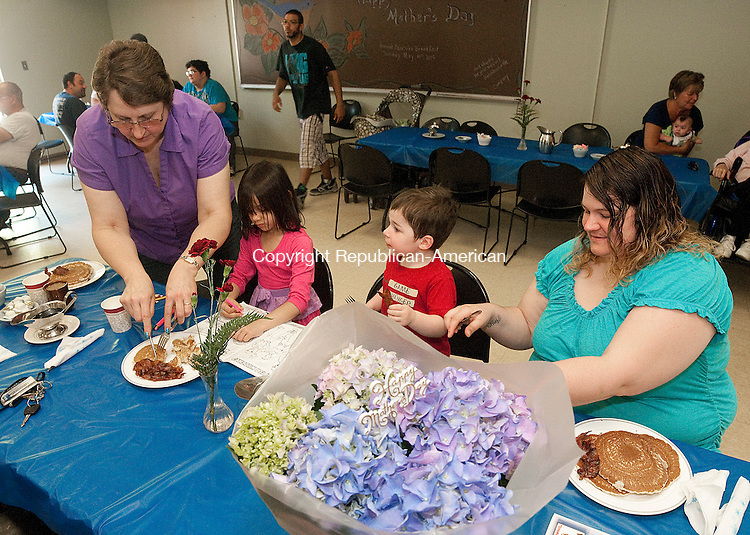 WOODBURY, CT--051015JS03- Heather Baker of Waterbury, right, along with her children Abel Maxwell, 2 and Anya Baker, 6, center, enjoy breakfast with Heather's mom, Carolyn Start of Woodbury, left, during the Hotchkissville Fire Co. of the Woodbury Volunteer Fire Department's 34th annual Mother's Day pancake breakfast held Sunday at the Emergency Services Building in Woodbury. <br /> Jim Shannon Republican-American