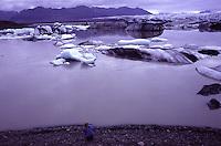 ISLANDA fiordo alle basi del ghiacciaio Vatnajokull, situato nell'Islanda sudorientale è il più grande d'Europa per volume e il secondo per estensione. Nell'immagine: una donna fotografa il fiordo con pezzi di ghiaccio che galleggiano in acqua.