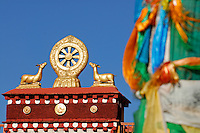 Dharmachakra, or Wheel of Law, represents the teachings of the Buddha and endless cycle of rebirth, flanked by deer atop the Jokhang Temple, with prayer-flag pole,  Lhasa, Tibet.