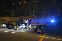 "Switzerland. The Republic and Canton of Neuchâtel. Neuchâtel. Narcotics squad. ""Narko"" operation. Blue emergency light on the roof of a police car riding down the street at night. Two police officers on duty (both in plain-clothes) control te car and identities of two french black men. The policemen look for illegal substances (drugs). Both black men will be left free at the end of the control. Plainclothes law enforcement is a method used by police. The policemen wear plainclothes or ""ordinary clothes"" instead of a uniform in order to avoid detection or identification as law enforcement agents. Police officers in plainclothes must identify themselves when using their police powers. 9.04.15 © 2015 Didier Ruef"