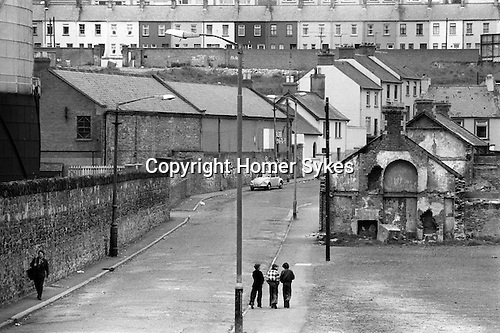 Derry Northern Ireland Londonderry. 1979. Catholic area of Derry, Tricolour painted on wall above the car. Stanleys Walk in the Bogside with the Old Gasyard to the left.