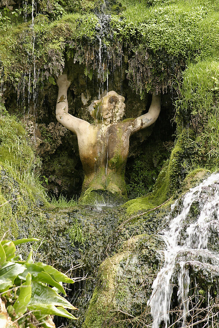 Classical sculpture of man under water and moss. Tivoli, Italy