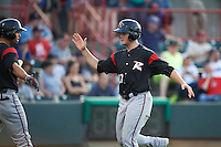 Richmond Flying Squirrels third baseman Christian Arroyo (22) congratulated by Ricky Oropesa (left) after scoring a run during a game against the Erie SeaWolves on May 27, 2016 at Jerry Uht Park in Erie, Pennsylvania.  Richmond defeated Erie 7-6.  (Mike Janes/Four Seam Images)