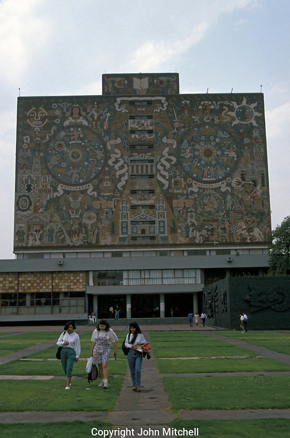 Female university students with the Central library in the background, Universidad Nacional Autonoma de Mexico or UNAM in Mexico City. The library is covered in murals by Juan O'Gorman. This university campus is a UNESCO World Heritage site.
