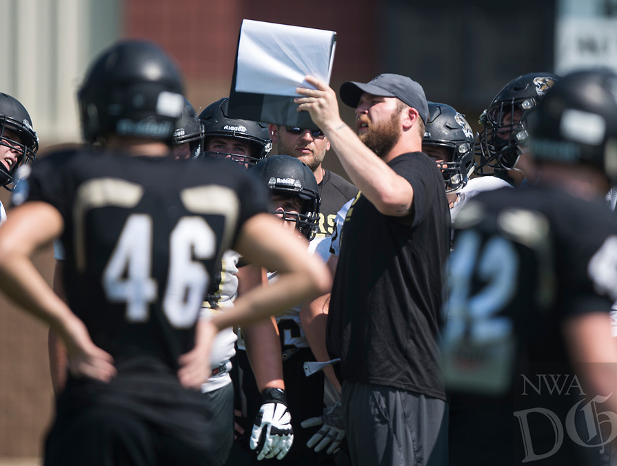 NWA Democrat-Gazette/CHARLIE KAIJO Assistant offensive lineman coach Markus Danenhauer goes over plays with defensive players during a football practice, Thursday, August 9, 2018 at Bentonville High School in Bentonville.