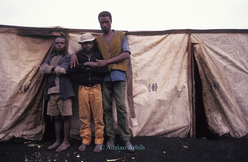 Forest  pygmies  (stand next to a tall Tutsi man) forcibly relocated due to the fighting  along the Rwanda/ Zaire border are  housed in temporary accomodation in the  refugee camps in Goma, Zaire.