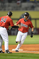 Birmingham Barons first baseman Rangel Ravelo (25) congratulated by manager Julio Vinas (54) after hitting a home run during a game against the Tennessee Smokies on April 22, 2014 at Regions Field in Birmingham, Alabama.  Birmingham defeated Tennessee 14-3.  (Mike Janes/Four Seam Images)