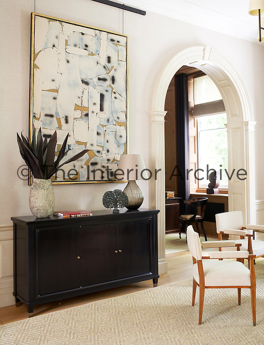 A large abstract artwork hangs above a dark sideboard in the living room
