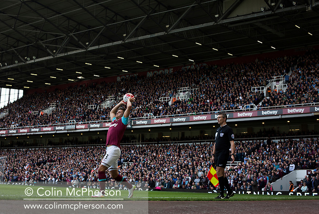 Home defender Aaron Cresswell taking a throw-in during the first-half at the Boleyn Ground as West Ham United hosted Crystal Palace in a Barclays Premier League match. The Boleyn Ground at Upton Park was the club's home ground from 1904 until the end of the 2015-16 season when they moved into the Olympic Stadium, built for the 2012 London games, at nearby Stratford. The match ended in a 2-2 draw, watched by a near-capacity crowd of 34,857.