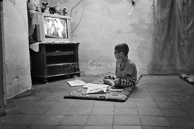 4.4..2015, Kirkuk,Iraq: Marwan can't move his eye's away from the tv while he has to do his homework .