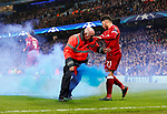 A Manchester City steward gets rid of a smoke bomb as Liverpool's players celebrate their opening goal during the Champions League Quarter Final 2nd Leg match at the Etihad Stadium, Manchester. Picture date: 10th April 2018. Picture credit should read: David Klein/Sportimage