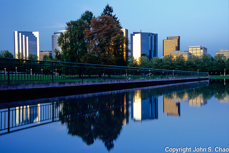 Downtown Bellevue's skyline mirrored in a reflecting pool at dusk in Bellevue Downtown Park. Bellevue, WA.