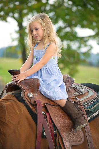 Pretty little blonde girl trying out her Grandma's big horse. Nikon D3s, 70-200mm.