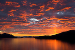 The clouds appear to catch fire as the sun sets over Gambier Island in Howe Sound, just north of Vancouver, British Columbia, Canada.  Photo By Gus Curtis.