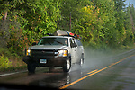 SUV with canoe on roof driving on wet road near Flathead Lake, Montana