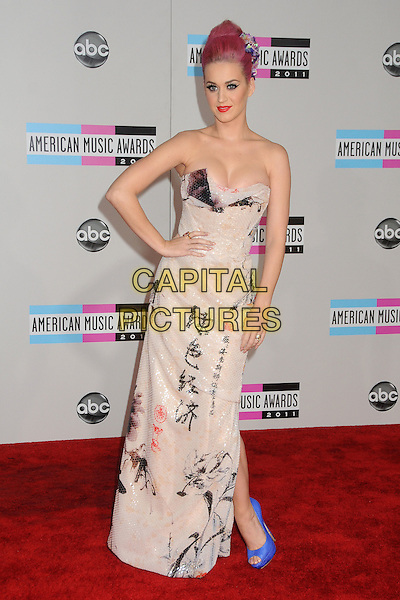 Katy Perry (wearing Vivienne Westwood).2011 American Music Awards - Arrivals held at Nokia Theatre LA Live, Los Angeles, California, USA..November 20th, 2011.ama amas ama's full length white Chinese sequins sequined draped dress strapless writing print blue peep toe snakeskin shoes hand on hip cleavage.CAP/ADM/BP.©Byron Purvis/AdMedia/Capital Pictures.