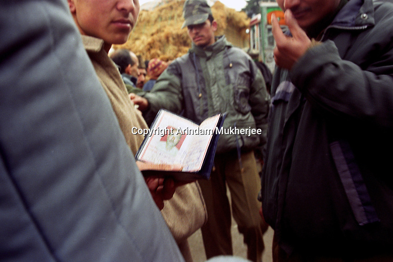 Security personnel checks papers specially provided to Jammu and Kashmir peopleat a security post near strategic town of Uri. Srinagar, Jammu and Kashmir, India. Arindam Mukherjee