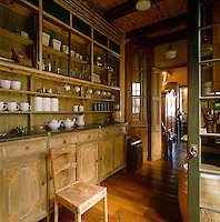 In the kitchen the matt surface of the antique cupboards creates a pleasing contrast to the polished floorboards