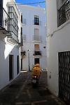 Motorbike alleyway whitewashed buildings in Vejer de la Frontera, Cadiz Province, Spain