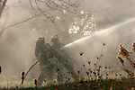 Two firefighters on the hose line spraying while getting drenched