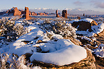 Balanced Rock, an Entrada sandstone rock formation, stands in snow in Arches National Park, near Moab, Utah, USA with the La Sal Mountains behind, with snowy rocks in the foreground.