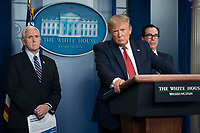 United States President Donald J. Trump delivers remarks on the COVID-19 (Coronavirus) pandemic alongside members of the Coronavirus Task Force in the Brady Press Briefing Room at the White House in Washington, DC, March 25, 2020, in Washington, D.C.   At left is United States Vice President Mike Pence and at right is United States Secretary of the Treasury Steven T. Mnuchin.<br /> Credit: Sarah Silbiger / Pool via CNP/AdMedia