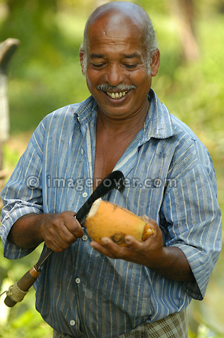 Smiling indian man opening a coconut with a large slasher (knife), Backwaters, Kerala.