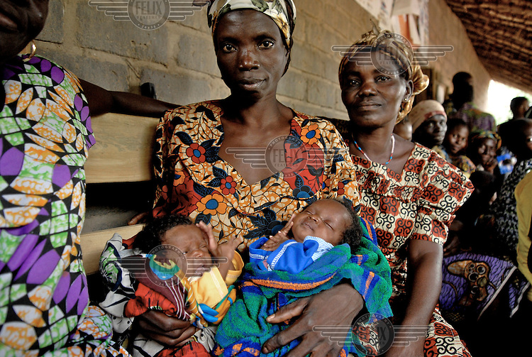 Two month old twins Sandrine and Olivia are held by Elaine, the traditional birth attendant who delivered them, with the mother Zaria sitting beside her, outside the Gervai health centre.