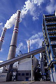 Pocerady, Czech Republic. Power station with smoking chimneys against a blue sky with white clouds.