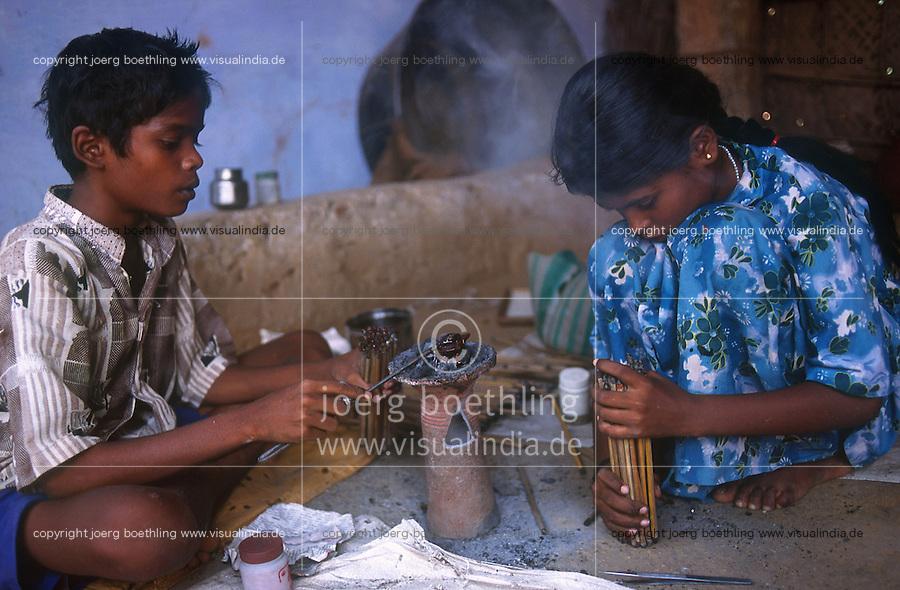 INDIA Tamil Nadu, Karur, child labour, boy and girl work in a polishing unit for artificial synthetic gems, they are putting the stones on bamboo sticks with wax before polishing / INDIEN, Kinderarbeit, Junge und Maedchen arbeiten in einer kleinen Edelsteinschleiferei im Dorf V. Pudur bei Karur, hier werden Halbedelsteine und kuenstliche Edelsteine poliert