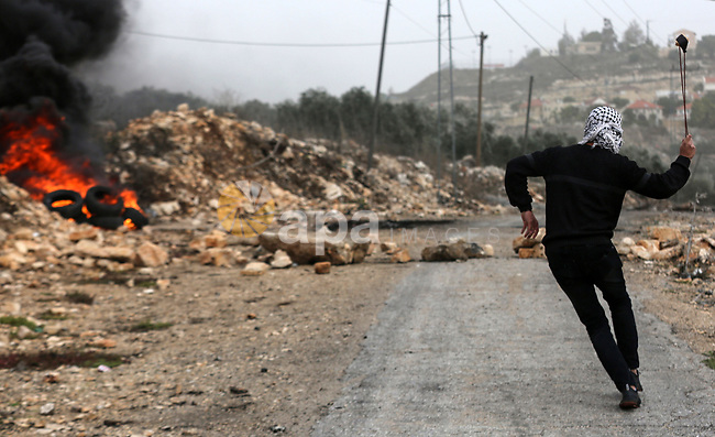 A Palestinian protester hurls a stone towards Israeli security forces during clashes following a weekly demonstration against the expropriation of Palestinian land by Israel in the village of Kfar Qaddum, near the West Bank city of Nablus on December 13, 2019. Photo by Shadi Jarar'ah