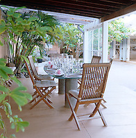 A table laid for lunch on one of several shaded terraces which surround the property