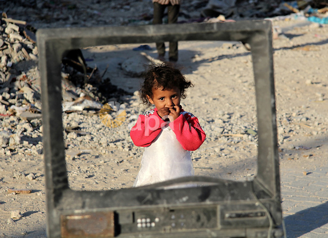 A Palestinian child looks through a damaged Television in front of his family house which destroyed during the 50-day war between Israel and Hamas militants in the summer of 2014, in the Gaza Strip town of Beit Hanun on April 25, 2015. Photo by Nidal Alwaheidi