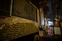 A woman prepares offerings at the Polar Palace, which is Taiwan's first temple of sea gods, in Tainan, Taiwan, 2015.