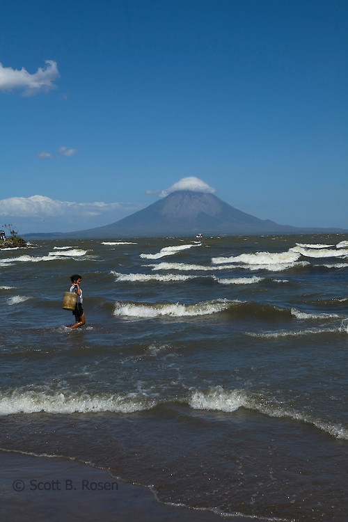 A Nicaraguan woman carries a bucket to fill water from Lake Cocibolca (across from la Isla de Ometepe), San Jorge, Nicaragua